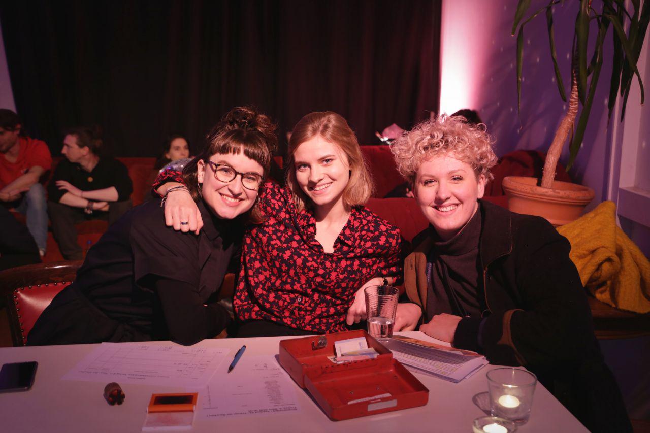 Drei Menschen sitzen an der Kasse, lächelnd